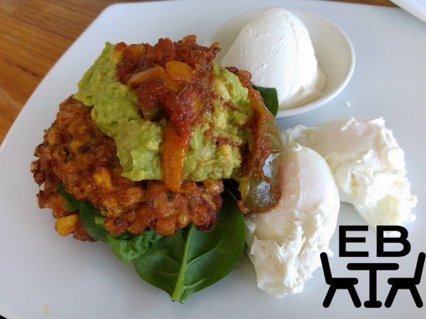 Sweet corn, ginger, and chive fritters with poached eggs, smashed avocado, sour cream, and capsicum relish.